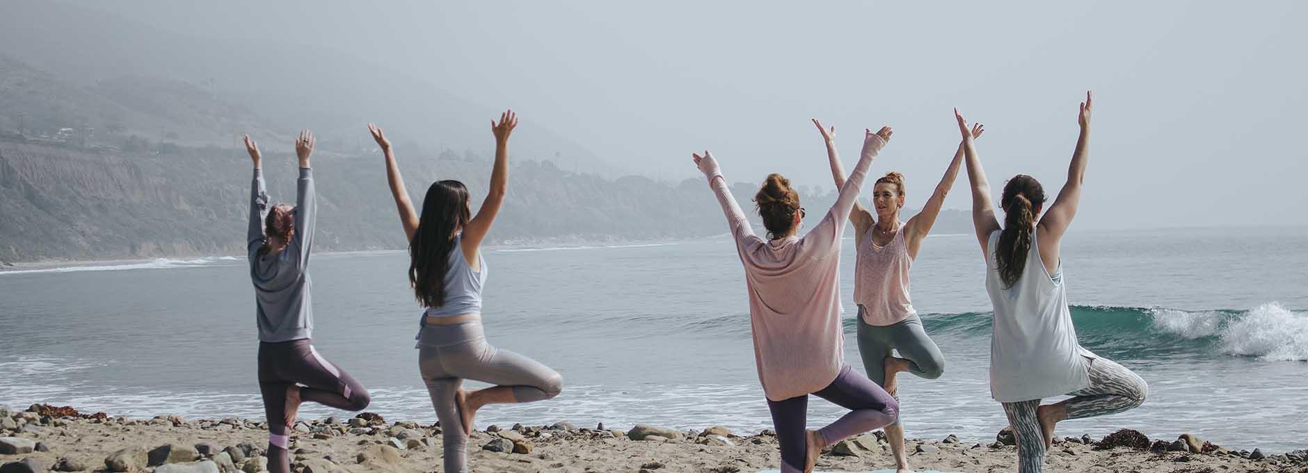 Women on beach doing Yoga