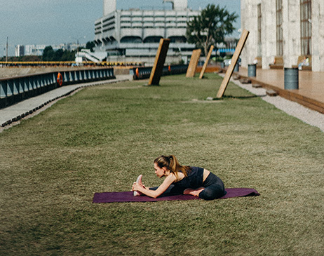 Woman doing yoga on grass outside office
