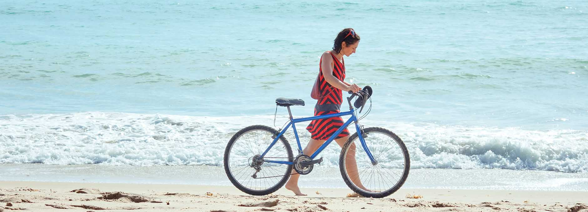Woman walking on beach with bicycle