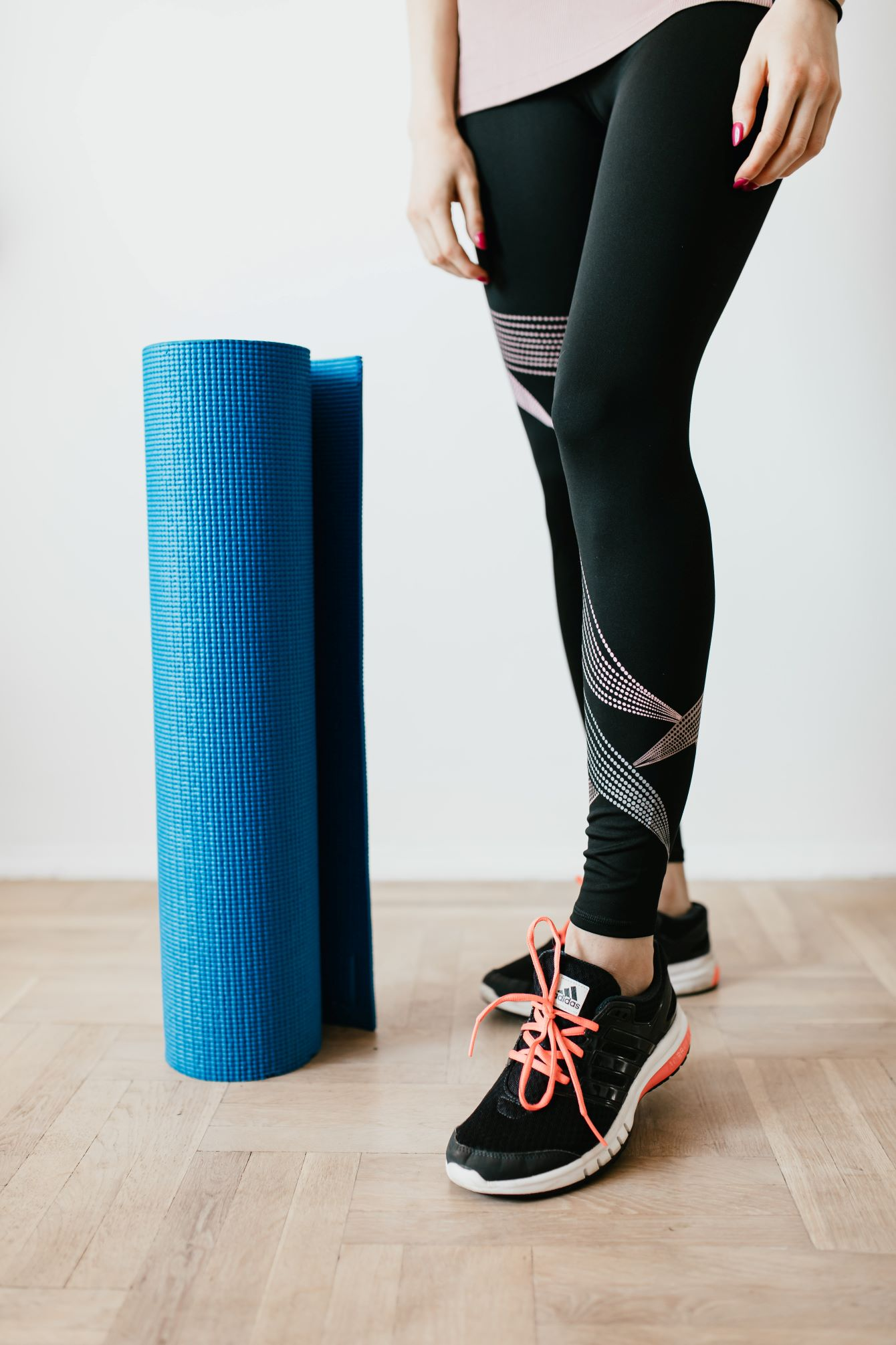 Woman standing next to yoga mat in activewear